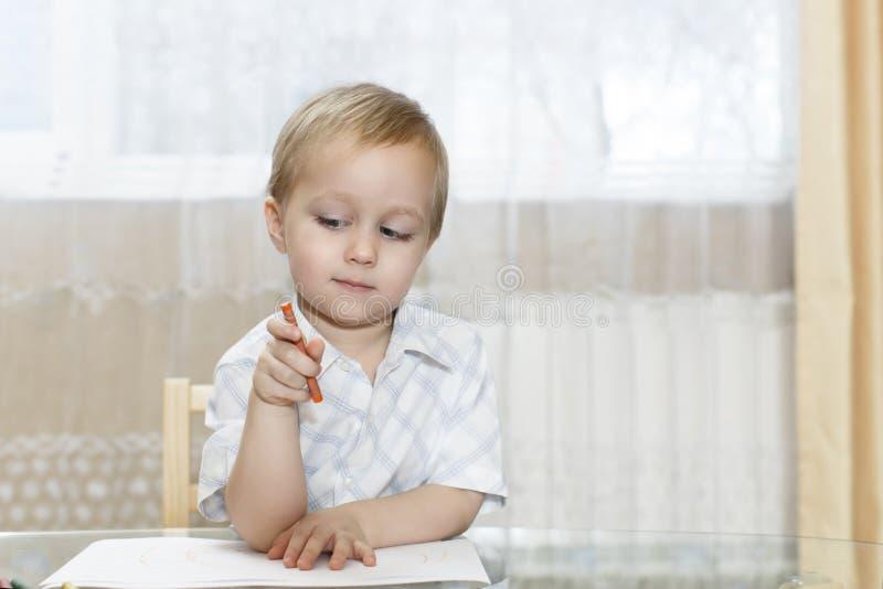 Weinig jongen trekt in kleurrijke potloden stock foto