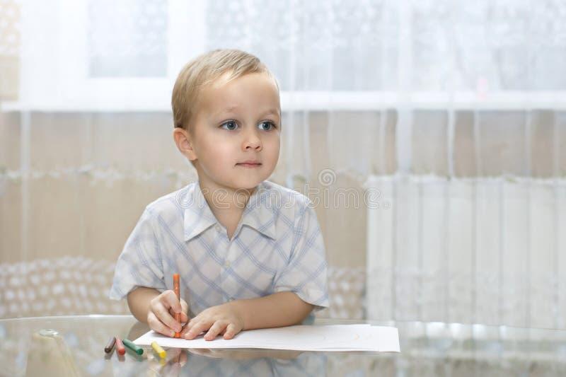 Weinig jongen trekt in kleurrijke potloden stock afbeeldingen