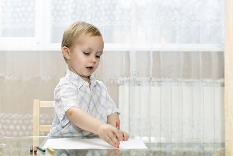 Weinig jongen trekt in kleurrijke potloden royalty-vrije stock afbeeldingen