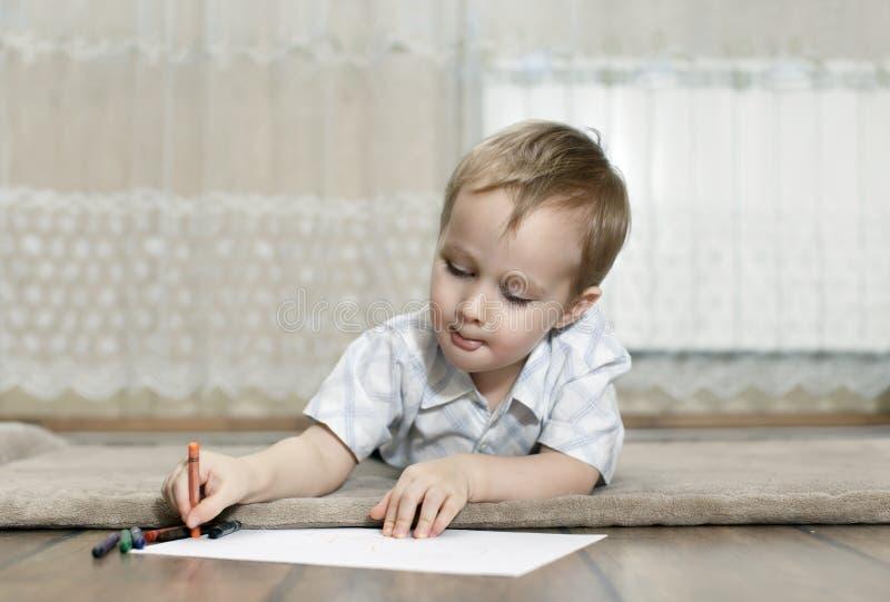 Weinig jongen trekt met kleurrijke potloden stock afbeeldingen