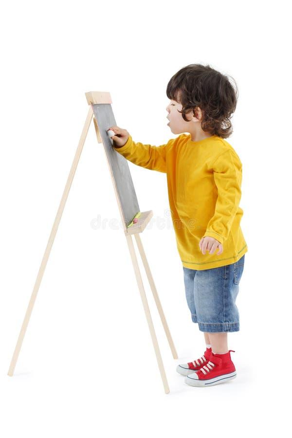 Weinig jongen trekt met krijt op geïsoleerd bord stock foto