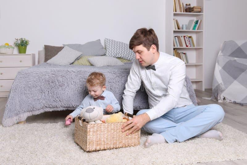 Weinig jongen, vaderspel met speelgoed in mand op tapijt stock afbeelding