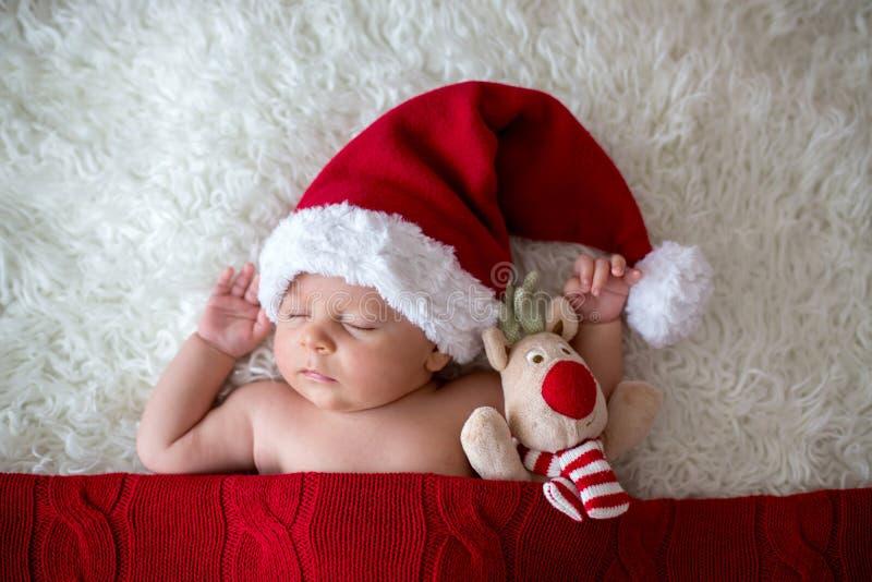 Weinig jongen van de slaap pasgeboren baby, die Kerstmanhoed dragen royalty-vrije stock foto's