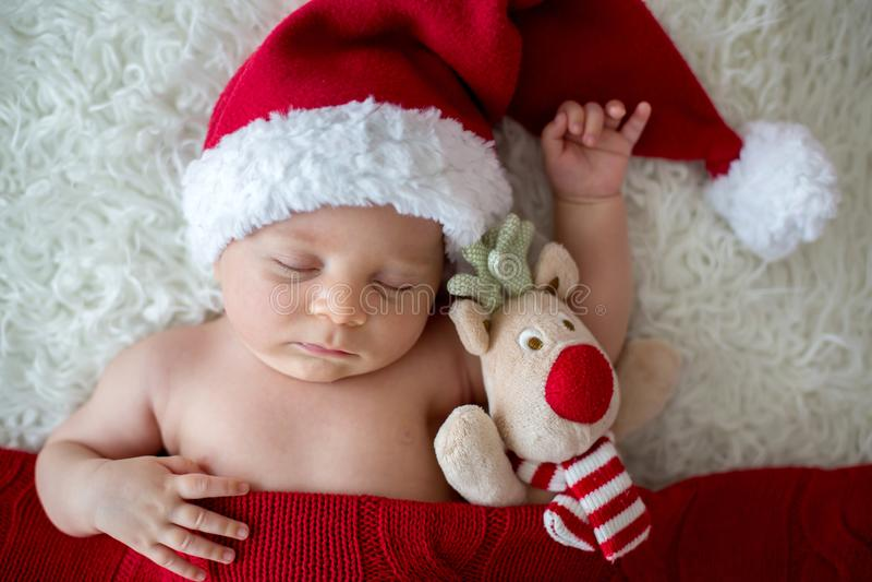 Weinig jongen van de slaap pasgeboren baby, die Kerstmanhoed dragen stock afbeeldingen