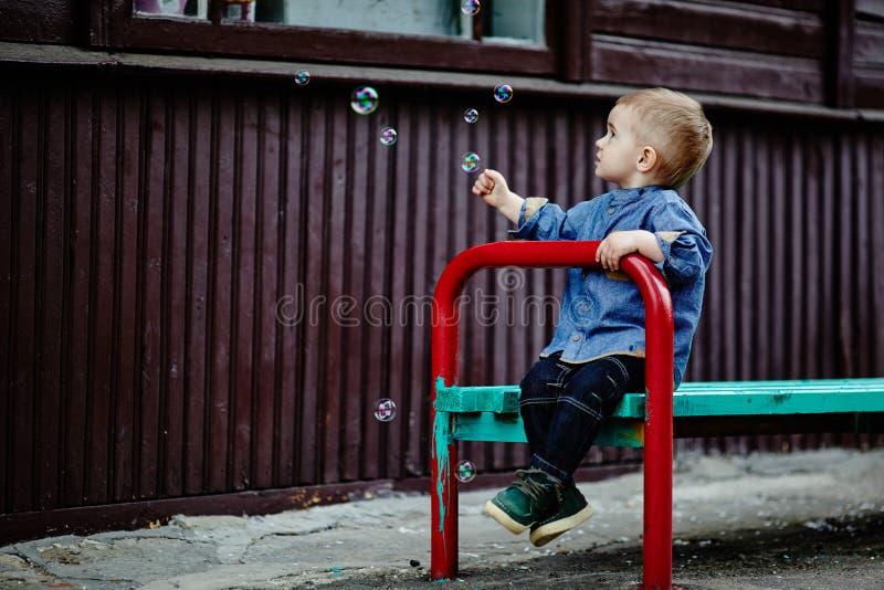 Weinig jongen vangt bellen zittend op bank stock foto