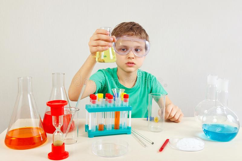 Weinig jongen in veiligheidsbeschermende brillen die chemische experimenten in laboratorium doen stock foto's