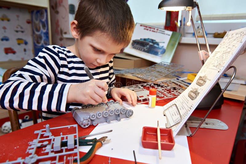 Weinig jongen verzamelt plastic modeltank stock fotografie