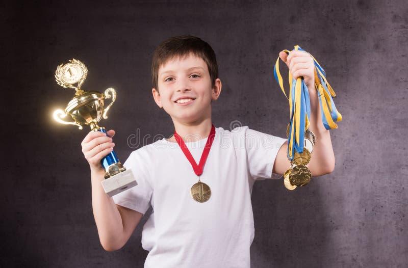 Weinig jongen viert zijn gouden trofee stock afbeeldingen