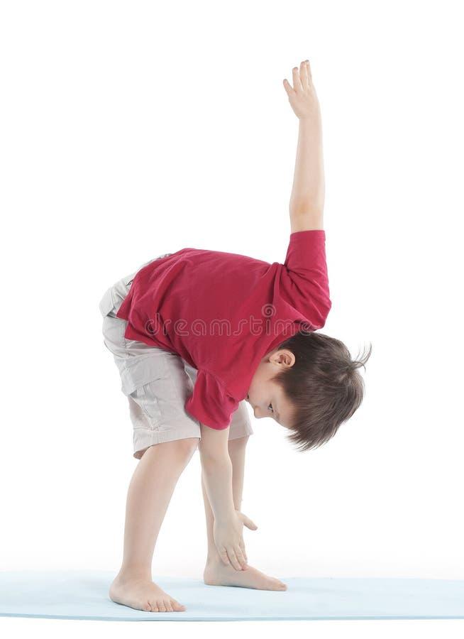 Weinig jongen voert een oefening uit om de spieren uit te rekken Geïsoleerd op wit royalty-vrije stock foto's