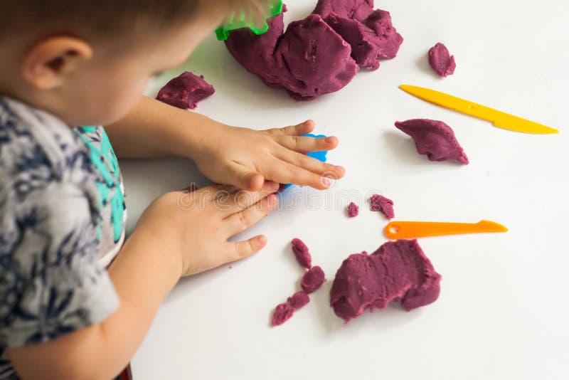 Weinig jongen vormt van plasticine op lijst, Kindhanden die met kleurrijke klei spelen stock fotografie