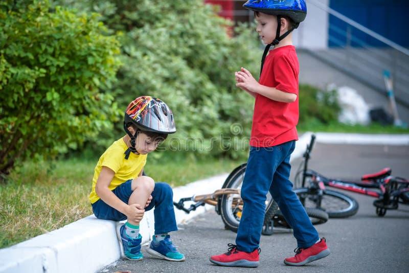 Weinig jongen weg gevallen van zijn fiets Ongelukkige jongenszitting op asphal royalty-vrije stock afbeeldingen