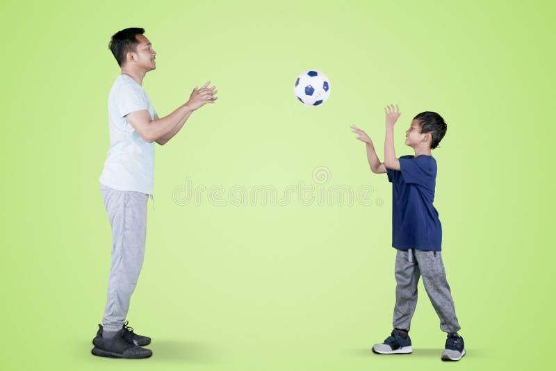 Weinig jongen werpt een voetbalbal aan zijn vader stock foto