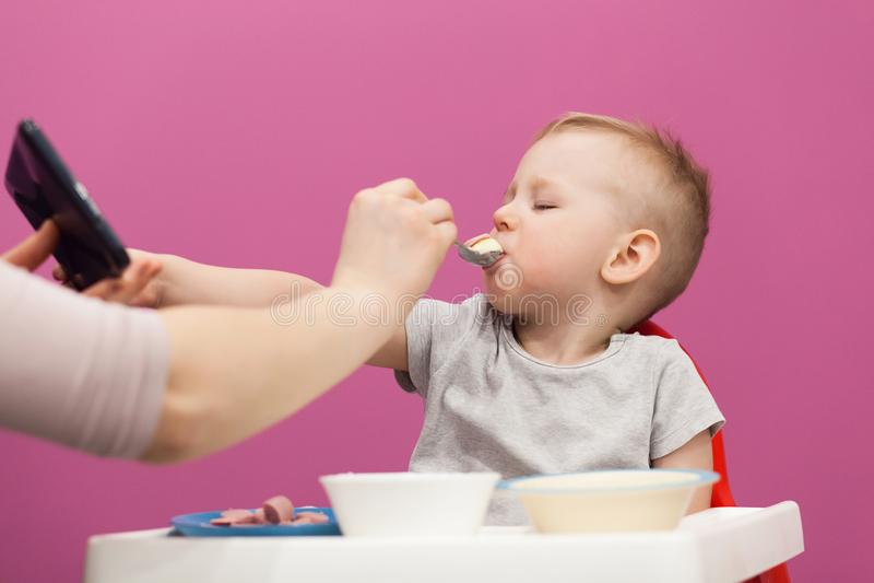Weinig jongen wil geen Fijngestampte aardappels eten Het kind eet ontbijt thuis, terwijl het letten op beeldverhaal op tablet stock foto's