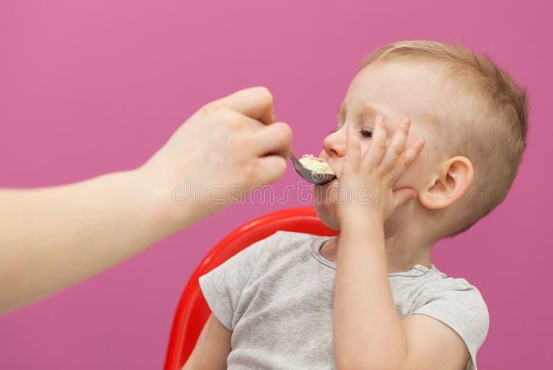 Weinig jongen wil geen Fijngestampte aardappels eten Het kind eet ontbijt thuis, terwijl het letten op beeldverhaal op tablet royalty-vrije stock foto's
