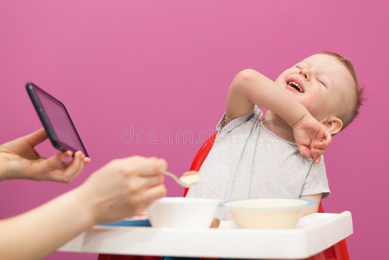 Weinig jongen wil geen Fijngestampte aardappels eten Het kind eet ontbijt thuis, terwijl het letten op beeldverhaal op tablet stock foto