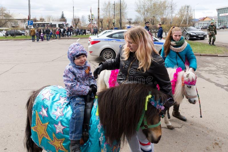 Weinig jongen zit op een poney, bevindt een meisje zich naast haar, tegen de achtergrond van een politiewagen stock afbeeldingen