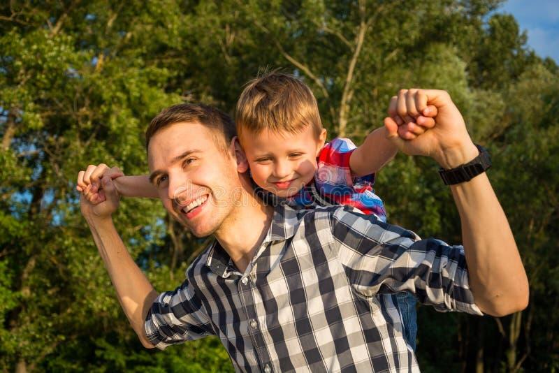 Weinig jongen zit op schouders zijn papa terwijl het imiteren van F royalty-vrije stock afbeeldingen