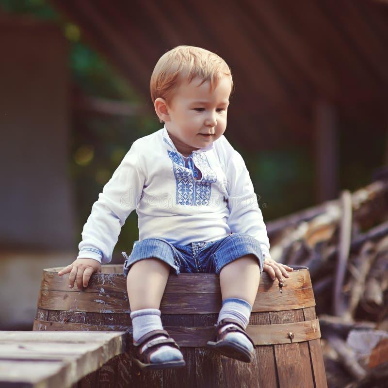 Weinig jongen zit op vat in het dorp royalty-vrije stock foto's