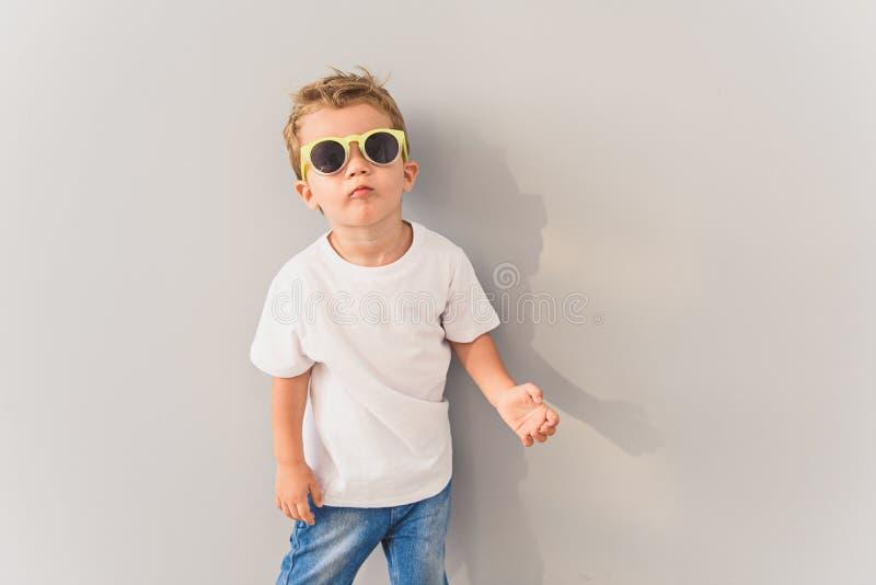 Weinig jongen in zonnebril die in studio stellen royalty-vrije stock foto