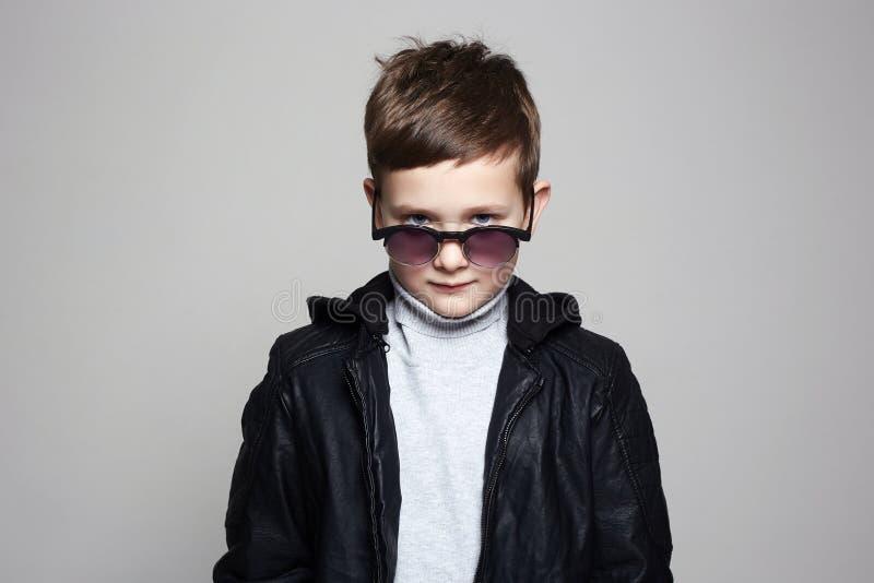 Weinig jongen in zonnebril modieus jong geitje in leer stock afbeelding
