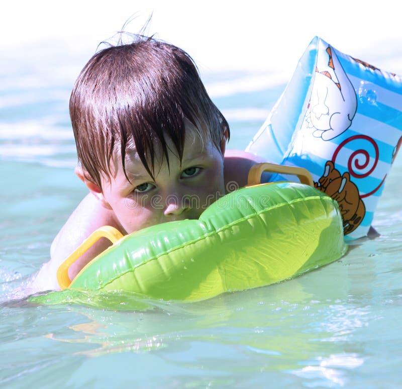 Weinig jongen in zwembad stock foto