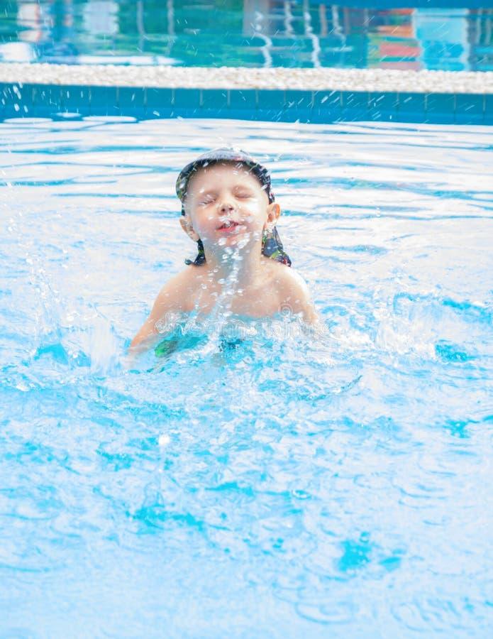 Weinig jongen zwemt, het vrolijke kind springen in de pool in de cirkel, openlucht zwembad, stock foto