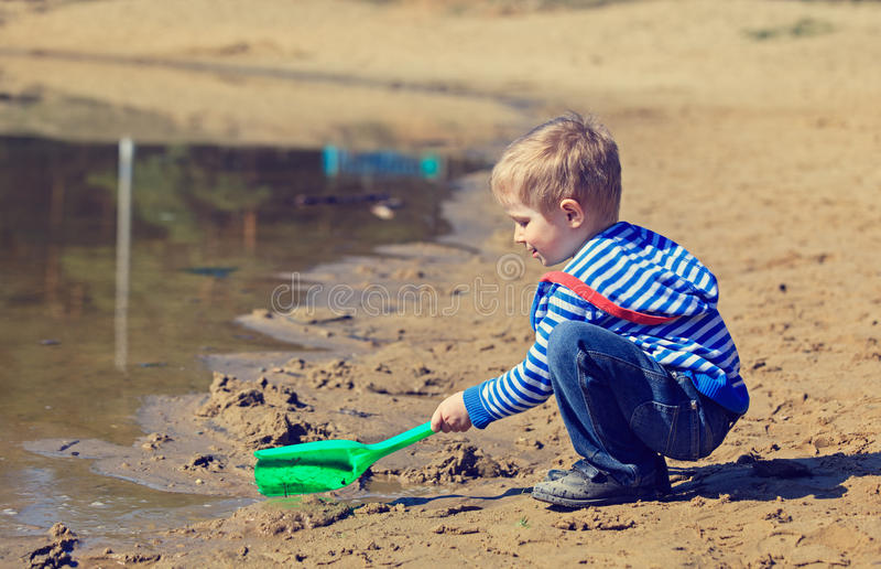 Weinig jongens gravend zand in de lente stock fotografie