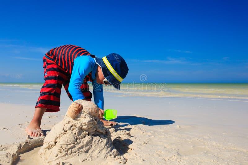 Weinig jongens gravend zand op tropisch strand stock fotografie