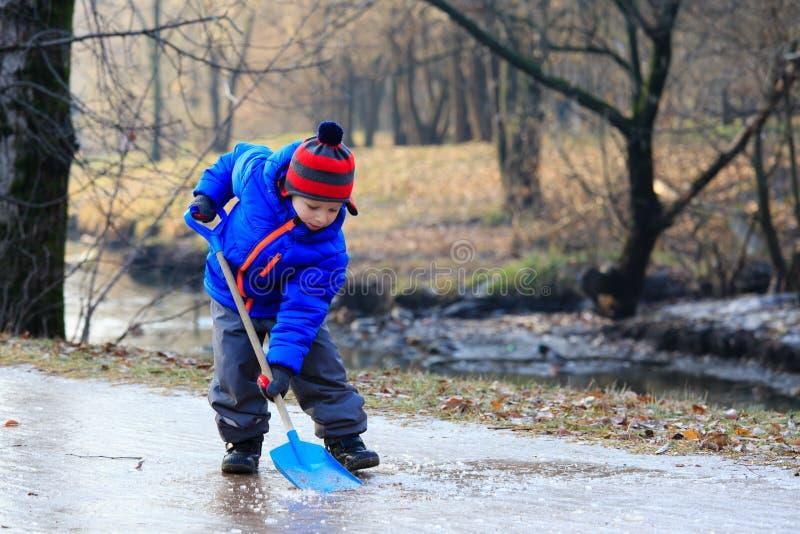 Weinig jongens schoonmakend ijs met spade royalty-vrije stock afbeeldingen