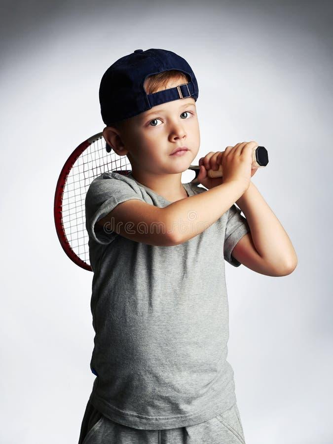 Weinig jongens speeltennis Sportjonge geitjes Kind met Tennisracket stock foto's