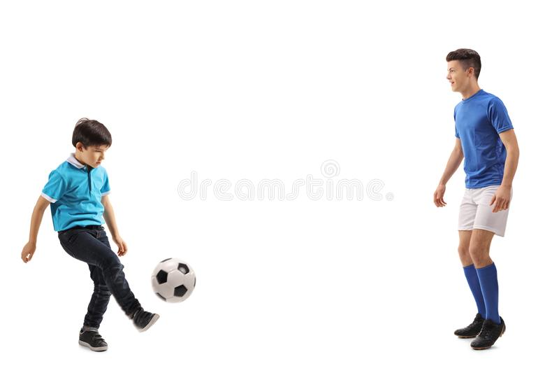 Weinig jongens speelvoetbal met een oudere jongen stock afbeelding