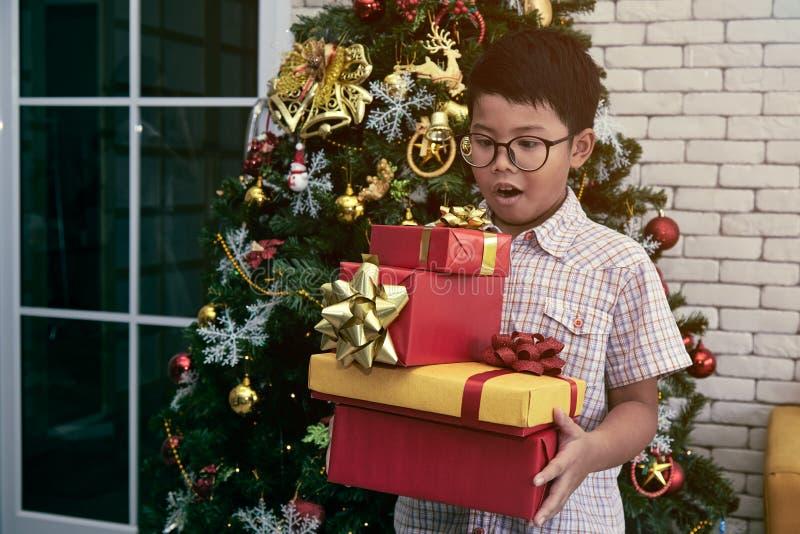 Weinig jongens status en verrassing terwijl het houden van heel wat giftdoos van Kerstmispartij in woonkamer royalty-vrije stock afbeeldingen