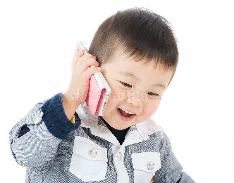 Weinig jongensbespreking aan mobiel royalty-vrije stock afbeelding