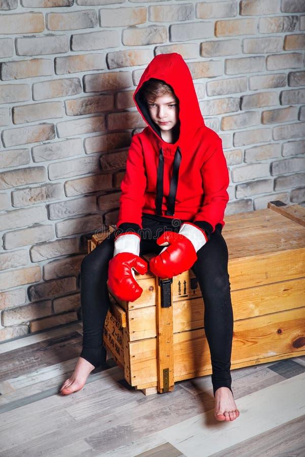 Weinig jongensbokser die met blondehaar zich in rood sweatshirt kleden die bokshandschoenen dragen die in een studio stellen royalty-vrije stock afbeeldingen