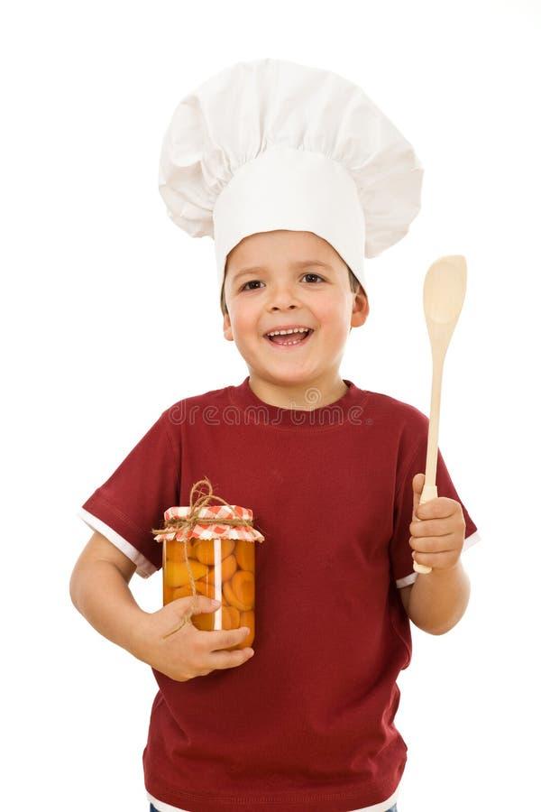 Weinig jongenschef-kok met een kruik ingeblikt fruit royalty-vrije stock fotografie