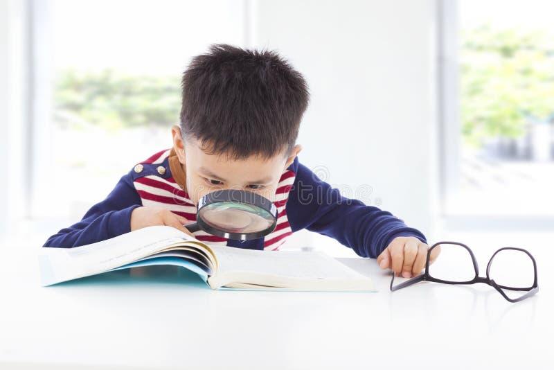 Weinig jongensdetective die aanwijzingen van boeken zoeken stock foto's