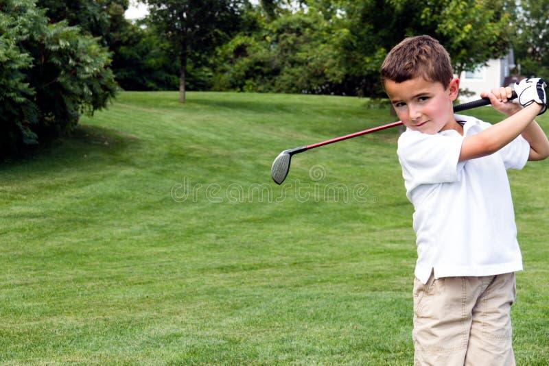 Weinig jongensgolfspeler die een club op de golfcursus slingeren stock foto