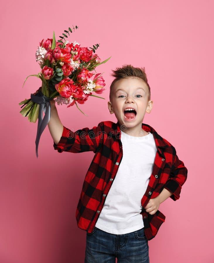 Weinig jongensjong geitje in jeans witte t-shirt en rood overhemd met een groot boeket van de lentebloemen wenst gelukkig met een stock foto