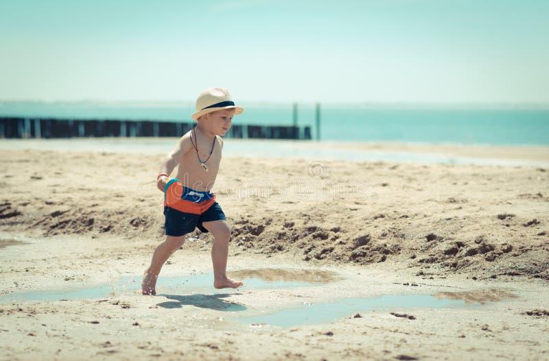 Weinig jongenskind die op het strand lopen die shell inspecteren stock foto