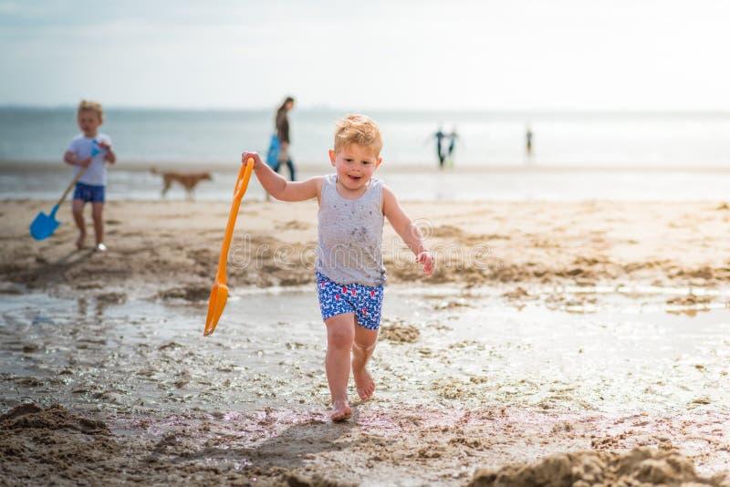 Weinig jongenskind die op het strand met tong lopen royalty-vrije stock afbeeldingen