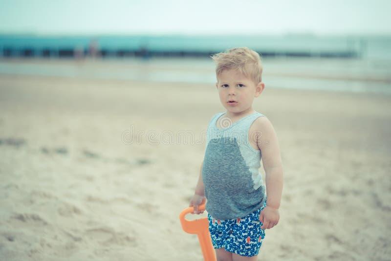 Weinig jongenskind die zich met een nat overhemd op het strand bevinden royalty-vrije stock afbeelding