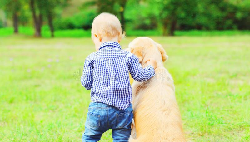 Weinig jongenskind en Golden retrieverhond samen in openlucht royalty-vrije stock afbeelding