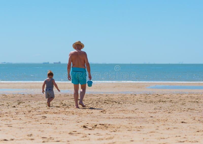 Weinig jongenskind met grootvader op het strand royalty-vrije stock afbeeldingen