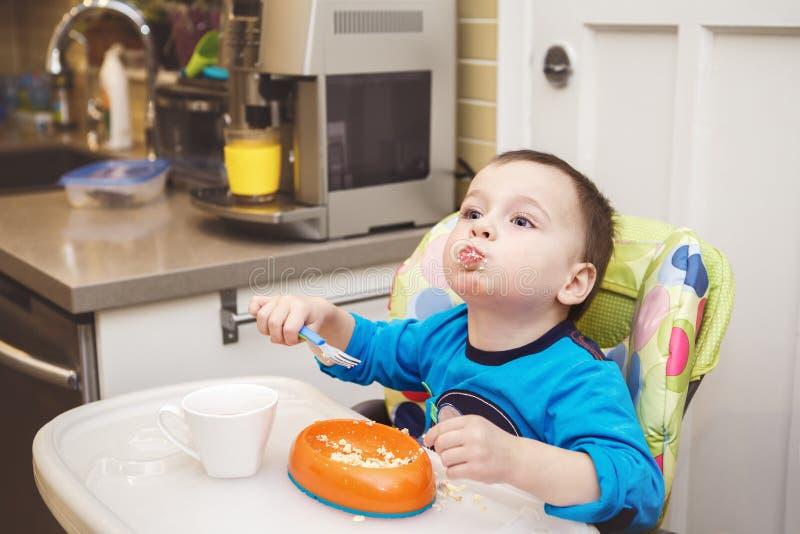 Weinig jongenspeuter die kwark eten die vork gebruiken royalty-vrije stock afbeeldingen