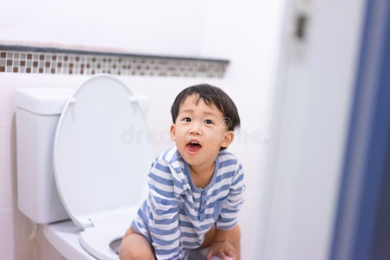 Weinig jongenspoo en plast in wit toilet royalty-vrije stock afbeelding