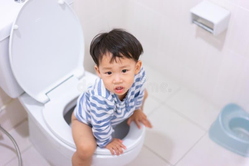 Weinig jongenspoo en plast in wit toilet stock foto