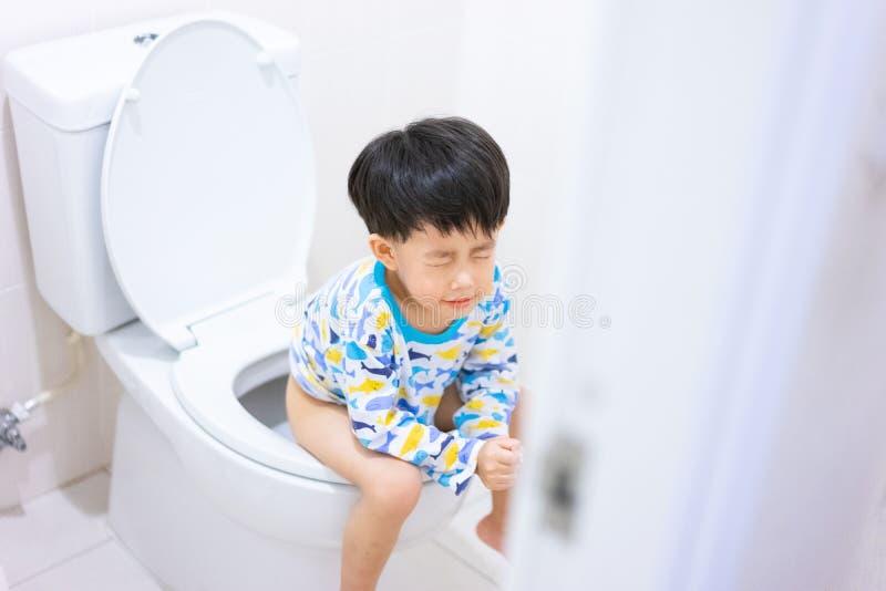 Weinig jongenspoo en plast in wit toilet royalty-vrije stock foto
