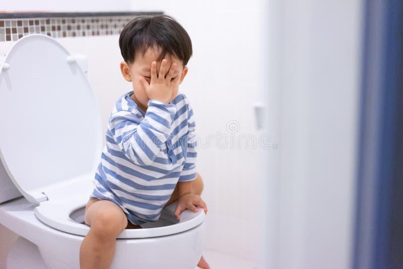 Weinig jongenspoo en plast in wit toilet stock foto's