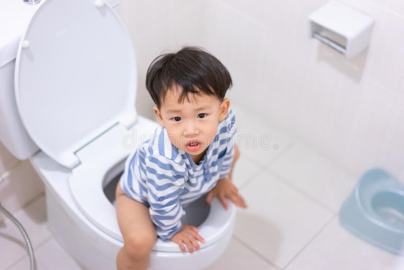 Weinig jongenspoo en plast in wit toilet stock afbeelding