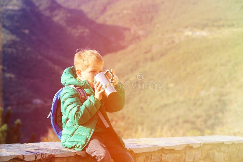 Weinig jongensreis in bergen die hete thee drinken stock afbeelding